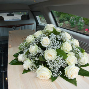 coffin with floral display in back of hearse