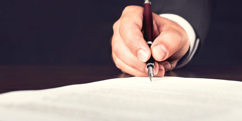 Male hand signing papers with fountain pen