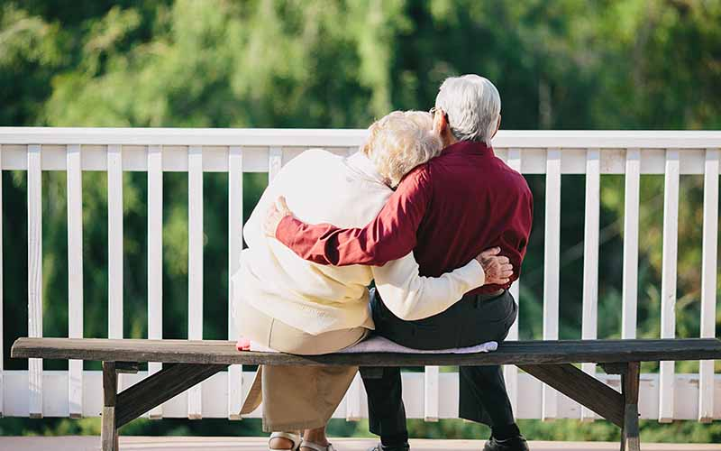 happy old couple sat on a bench